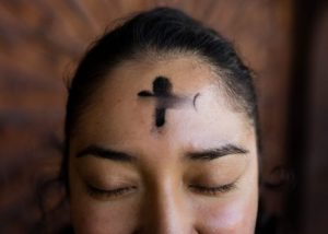 woman with black cross tattoo on her face