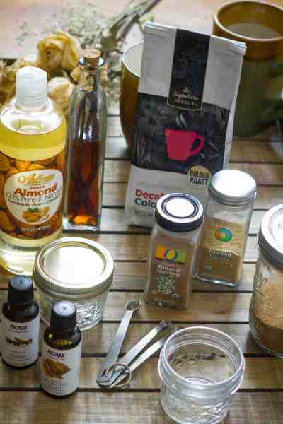 All the ingredients needed for a pumpkin spice latte sugar scrub- coffee, sugar, vanilla, essential oils, spices, almond oil, and more