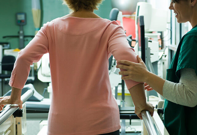 Woman learning to walk again with the help of a physical therapist