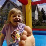 Bild Lachendes Mädchen auf Mini Hüpfburg Clown