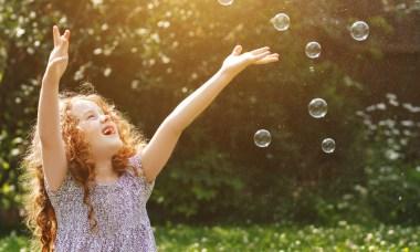 Kind jagt Seifenblasen von Seifenblasenmaschine