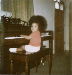 Me as a baby playing the piano with an afro