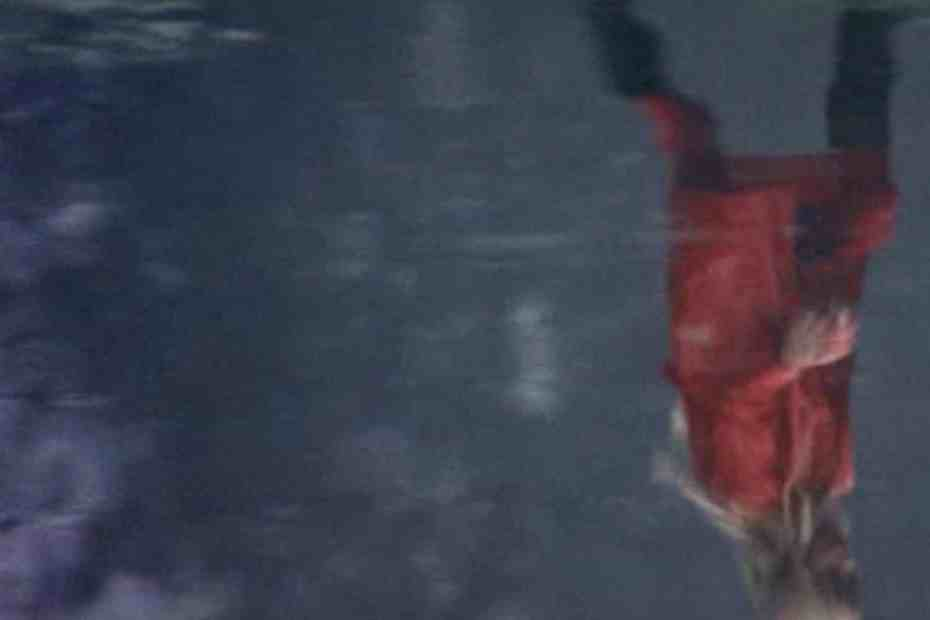 Reflection of Christine in red coat walking beside the water