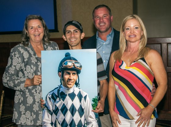 Jockey Jose A Garcia holding portrait he received at EARA dinner (with Uptown Sandy Girl connections )