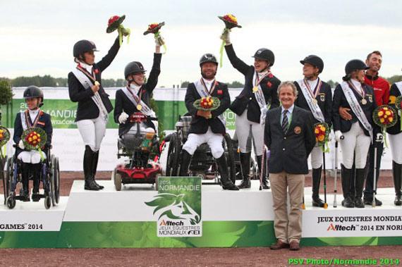Britain's victorious para-equestrian team celebrates on the podium.