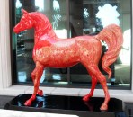 This bright red arabian is painted with an ornate, traditional gold pattern.