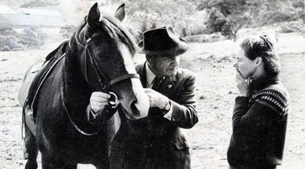 """Tom Roberts and Spring Song demonstrate """"feeling for the mouth"""" to Virginia Batten, Coromandel Valley, South Australia, 1972. Image by Webb McKelvey, published in Horse Control - The Young Horse."""