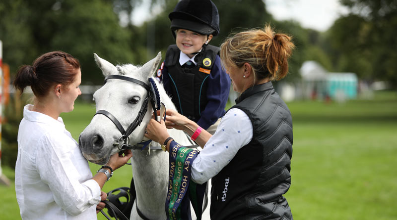 Nutkin and Darcy Fowler receive the champion's ribbon from eventer Piggy French, as Darcy's mum Leah looks on.