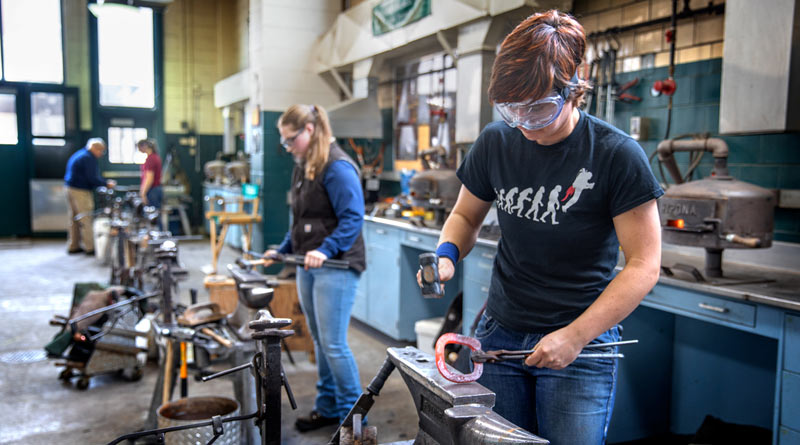 Kerry Spain (right) and Kahlan Schramm work at shaping horseshoes in the farrier shop.