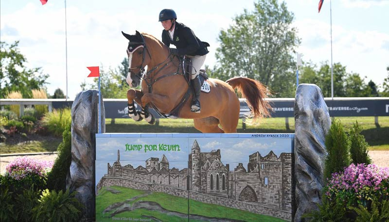 """Patrick McNamara and Billy Onslow soar over the Dalman Jump Co.-designed """"Jump for Kevin"""" wall en route to winning the $5,000 Kevin Babington Benefit Classic at the Silver Oak Jumper Tournament."""