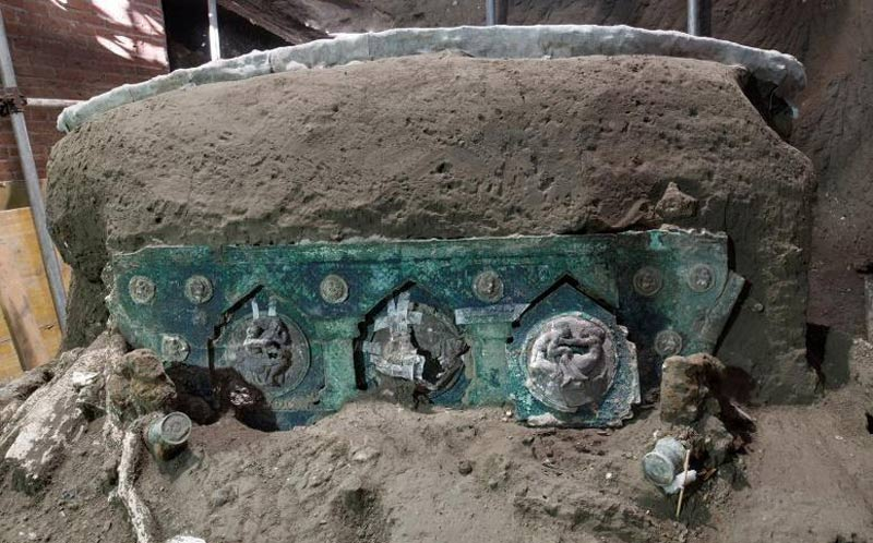 The upper section of the bronze sheet is decorated with small tin medallions, which depict cupids engaged in various activities.