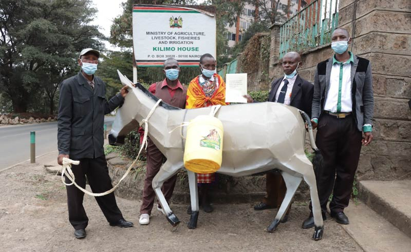 Donkey owners, including Joseph Thendu (second from right), from Alliance for Donkey Workers of Kenya (ADWOK) hand in a petition to the Government to ask for a fresh ban on the donkey skin trade.