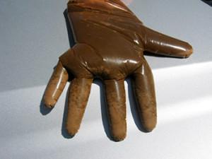 de zandtest: zand zakt uit de mest in de vingers van de handschoen
