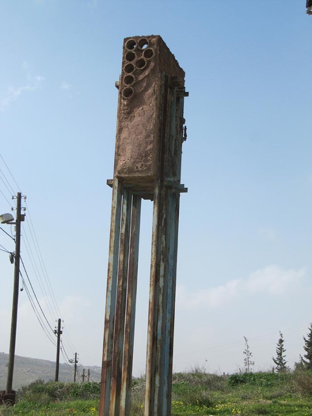 """פסל סביבתי של טומרקין שהוקם כהפגנה נגד הקמת הישוב. האת """"P"""" מסמל שלום או אולי פלסטין."""