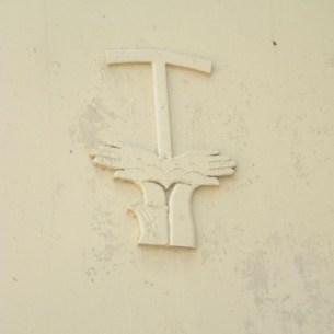 וריאציה על סמל הפרנציסקנים, המופיעה על דלת בחומת כנסיית הביקור בעין כרם. הסמל מציג את השרוול שעל הזרוע האחת (=פרנציסקוס); והזרוע החשופה מצד שני (=ישו). מה שמאוד בולט הוא הזווית הלא טבעית של כפות הידיים, שנועדו להציג את הסטיגמטה - חורי המסמרים הן אצל ישו והן אצל פרנציסקוס. מעל הידיים, האות טאו שהייתה אהובה על פרנציסקוס בשל דמיונה לצלב. צילום: Almog