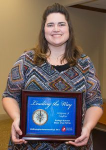 Melisha holding a Leading the Way plaque recognizing Ohio's Hospice of Dayton as a leader in blood donations.