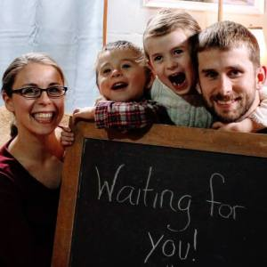 """mother, father, two children and a chalkboard sign with text """"waiting for you"""""""