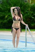 Casey Batchelor in a black bikini at a pool on holiday in the Dominican Republic