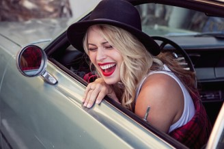 Young woman leaning out of car window, laughing