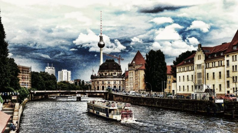A boat navigating the canal in Berlin with the Berliner Fernsehturm in the backdrop.