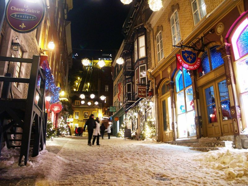 Petit Champlain in Quebec City on snowy holiday evening.