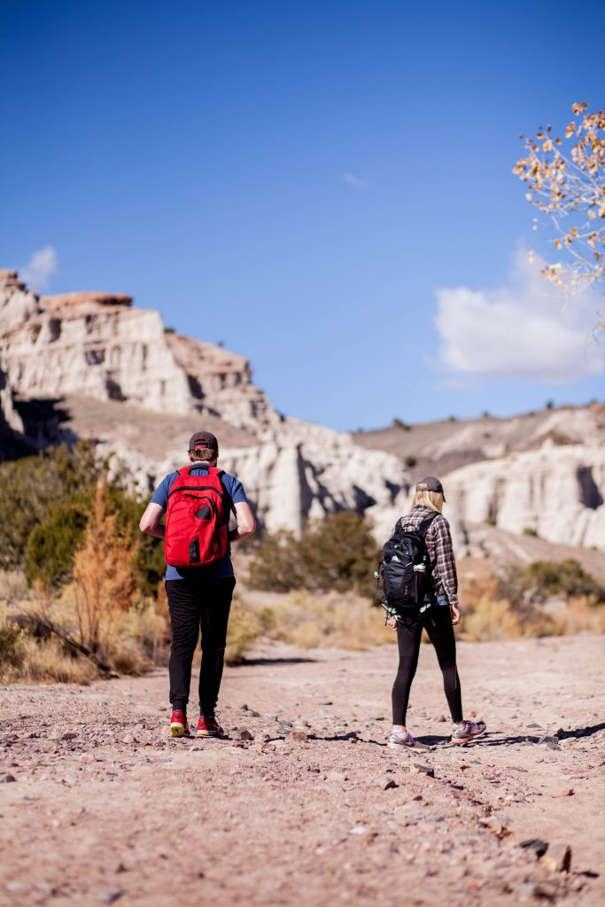 A young couple stands in a mountainous desert with backpacks about to begin their hike.
