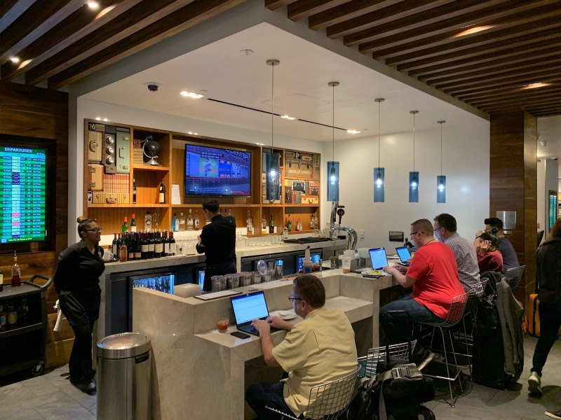 Business people and travelers work with drinks in hand at the AmEx Centurion Lounge in San Francisco International Airport.