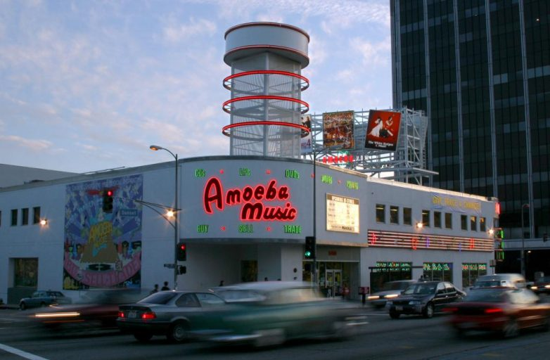 View of Amoeba Music exterior as cars whiz by on Sunset Boulevard in Hollywood, LA.
