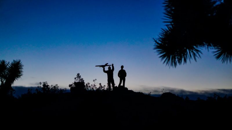 Silhouette of father teaching son how to fly an remote-control airplane while camping in Joshua Tree National Park.