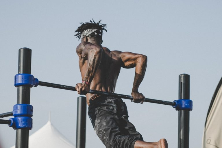Ripped man hoists his body up on outdoor gym bars with muscles rippling.
