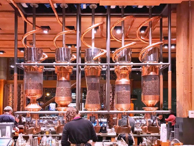 Giant copper coils wind down from the ceiling in coffee roastery.