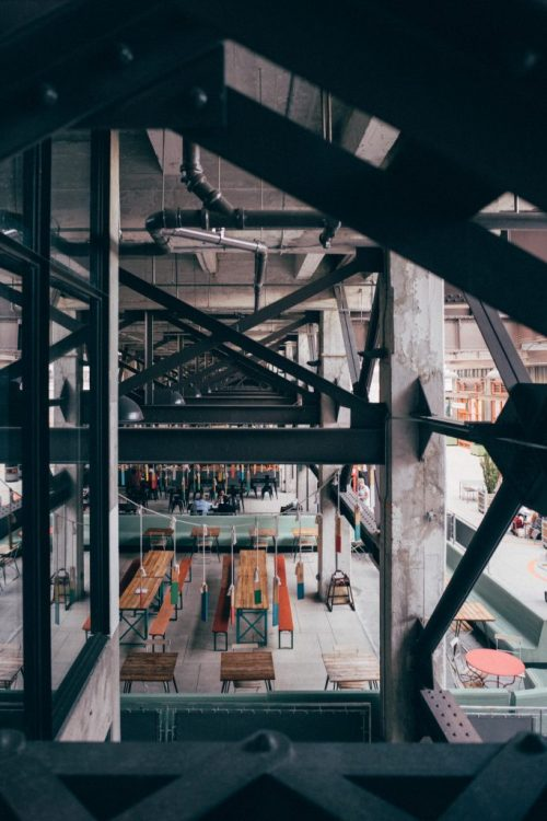 Side view of Ponce City Market in Atlanta framed through steel cross beams on a neutral overcast afternoon.