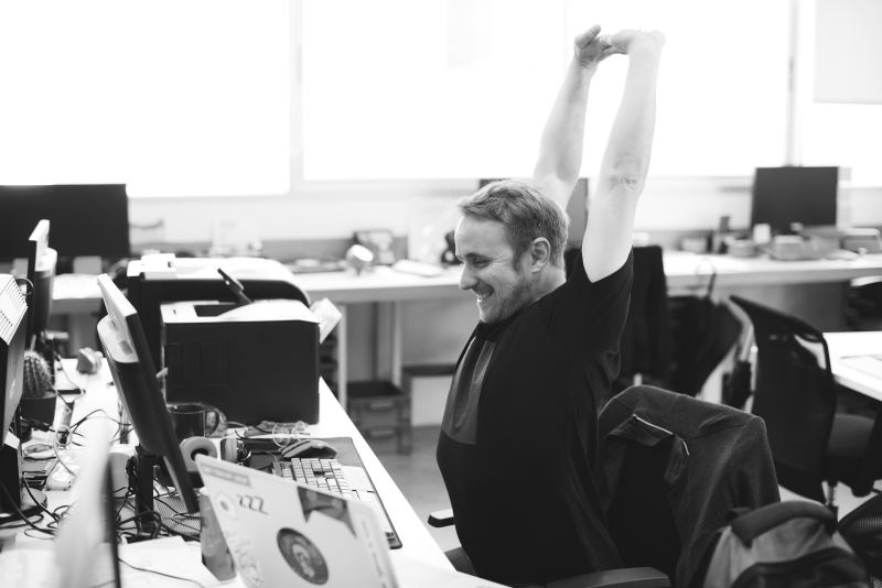 Office worker stretches his arms high and smiles after being productive and earning himself a much-deserved break.
