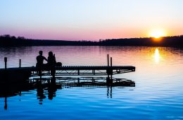 Silhouettes of two people sitting on dock watching the sun go down on the water.