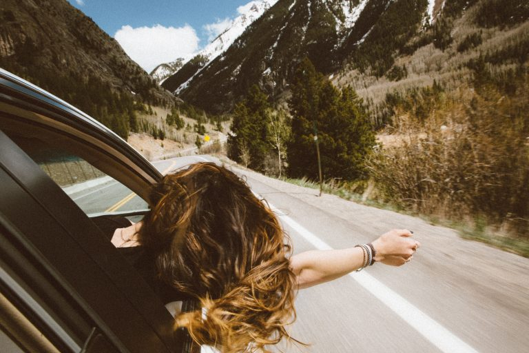 Woman sticking her head out of car window on highway during roadtrip through mountains.