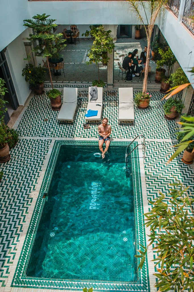 Man crosses legs in hotel courtyard pool during the day stay.