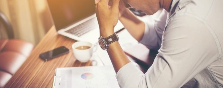 Worker sits at desk with coffee and report, hand on his head in stress.