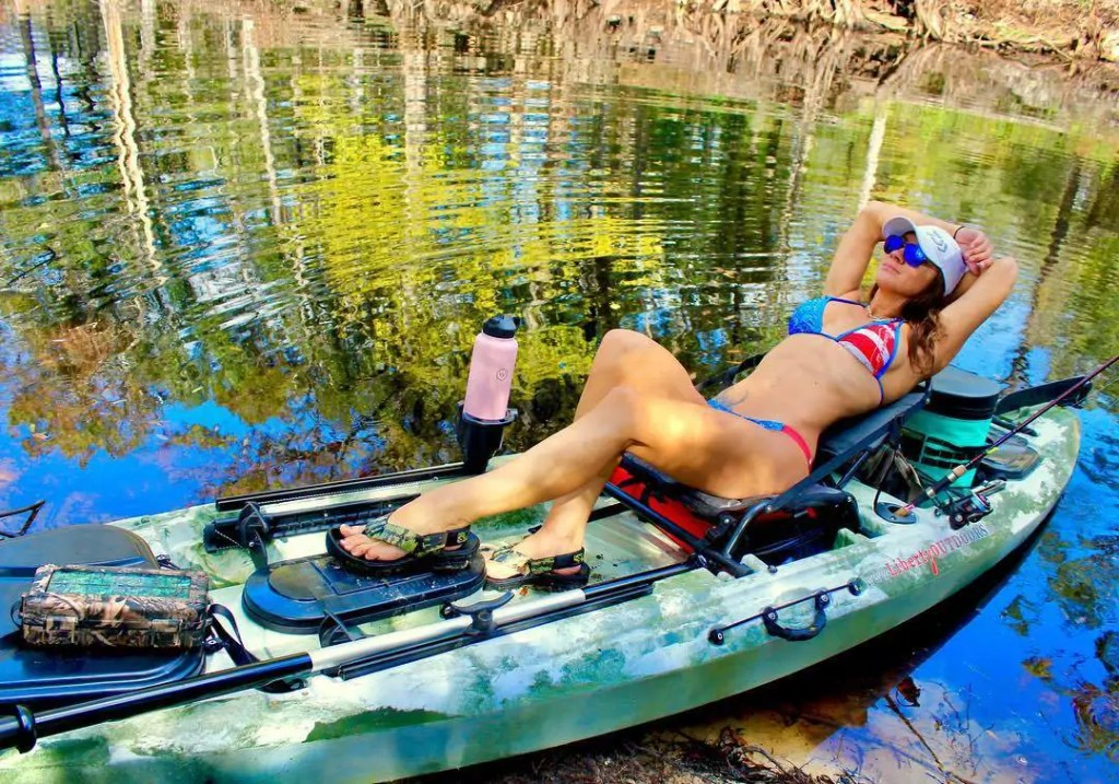 Fishing babe in a bikini relaxing in her kayak