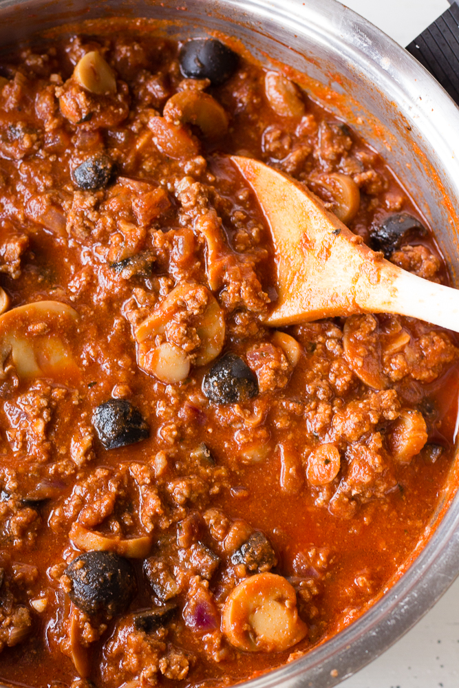 meat sauce with a wooden spoon in it