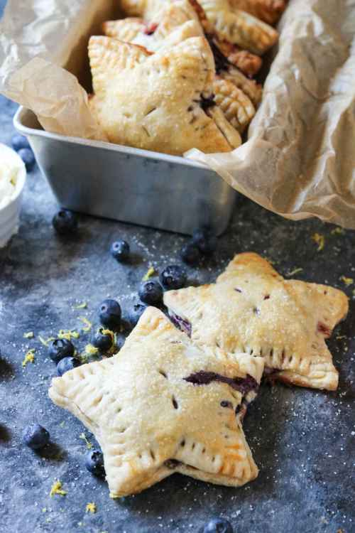 star shaped lemon blueberry mascarpone hand pies on a blue background with some in a silver tin.