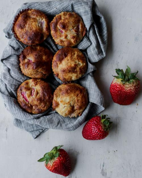 six whole grain strawberry muffins on a gray towel with three strawberry beside them