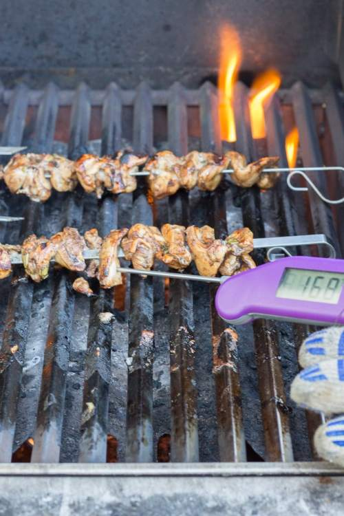 checking the temp of the gluten free teriyaki chicken kabobs on the grill