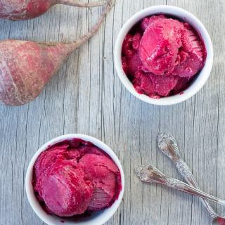 two white cups with honey roasted beet nice cream, and two beets in the upper left corner and two silver spoons in the bottom right corner