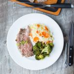 white plate with gluten free flank steak marinade with roasted broccoli and carrots and rice