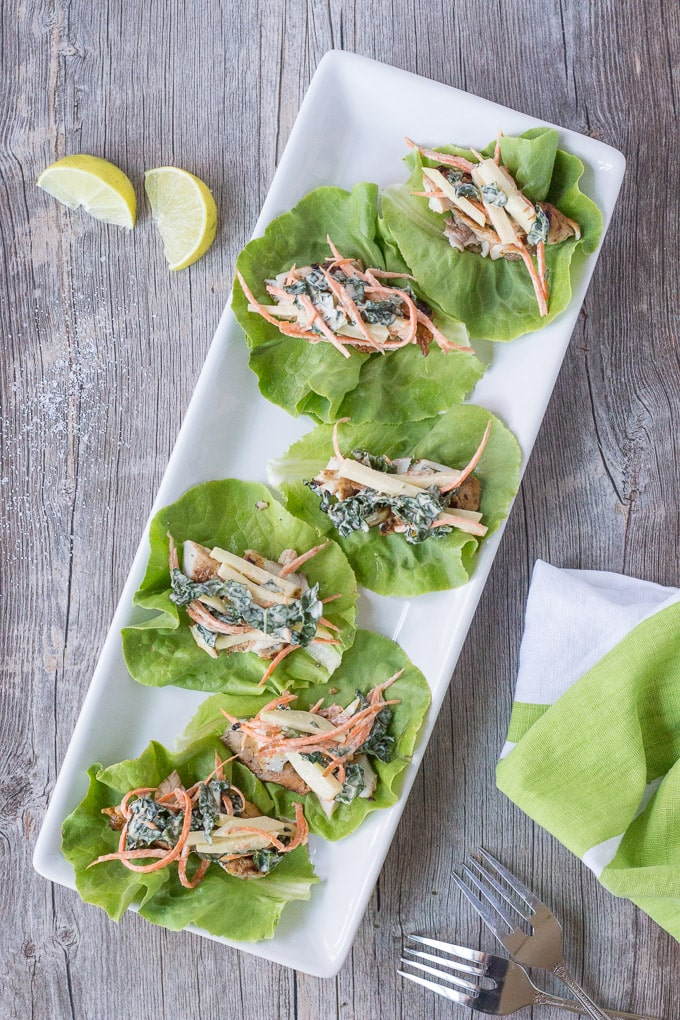 mini easy fish tacos on lettuce on a white rectangular platter