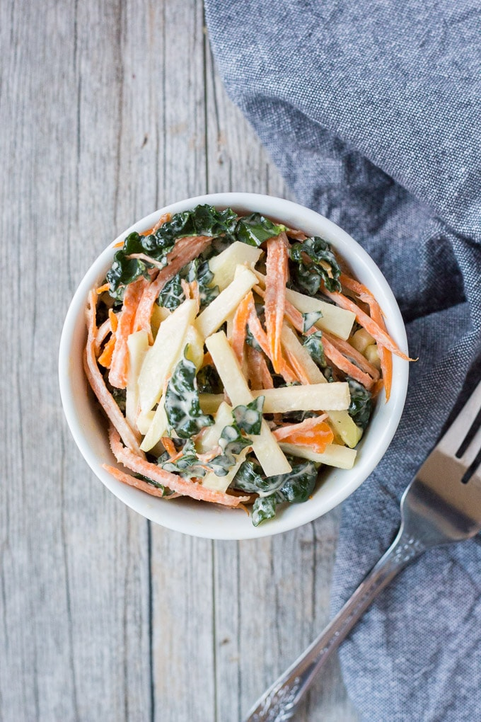 top down shot of kohlrabi, kale, and carrot coleslaw in a white bowl with a fork and gray towel