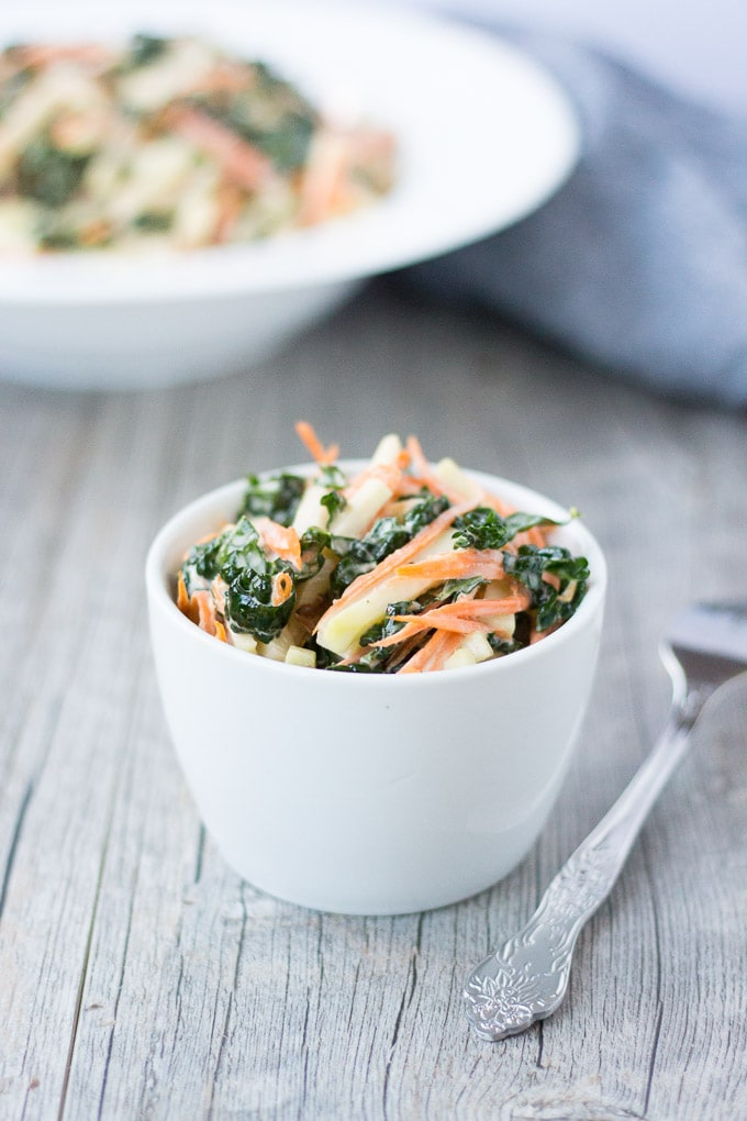 small white bowl of kohrabi, kale, and carrot coleslaw with a silver fork and a large white bowl and gray napkin in the background