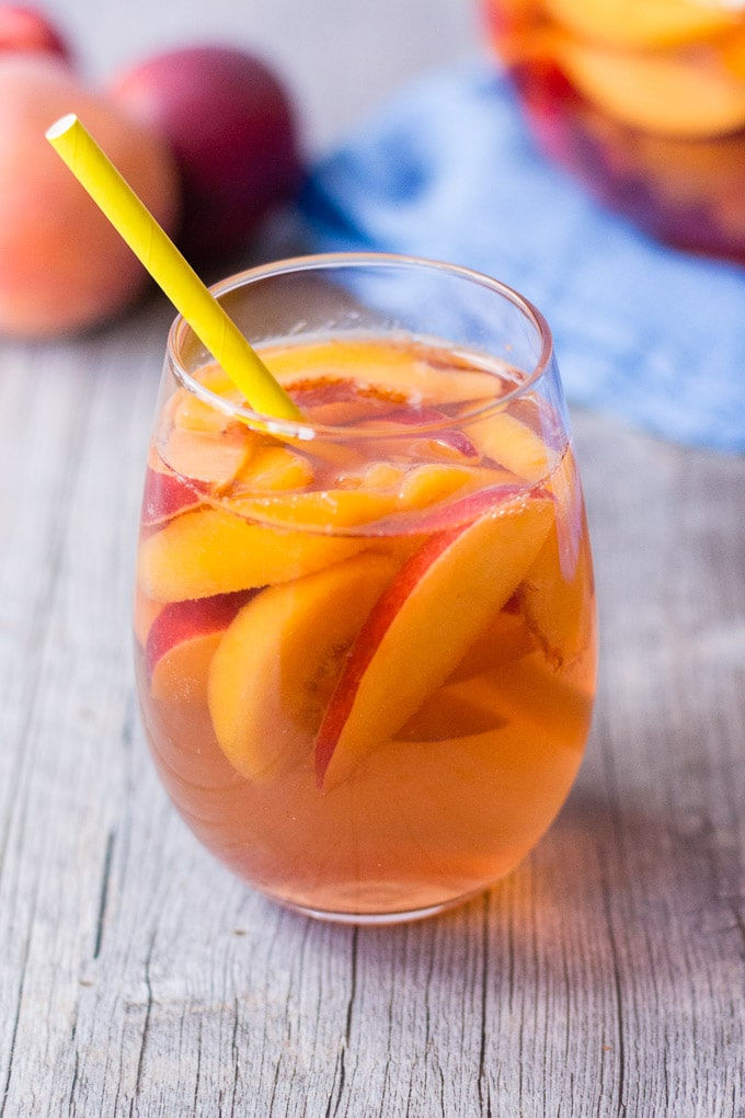 stemless glass of peach rose sangria with fruit in left background and clear pitcher with sangria on a blue towel in right background
