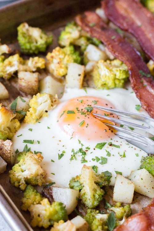 shot of a silver fork cutting into a cooked egg on a sheet pan with potatoes, romanesco, and bacon