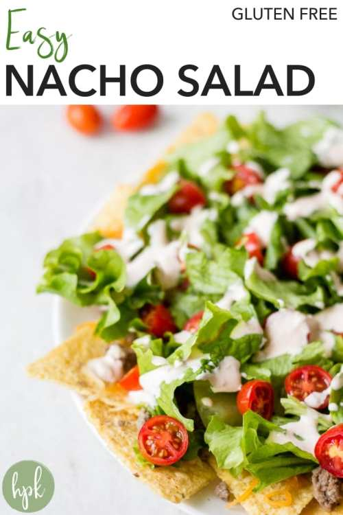 Need a super fast dinner option that incorporates veggies? Try this Easy Nacho Salad. It's a layered recipe with tortilla chips on the bottom, covered with meat and cheese, then lettuce and tomatoes on top. Finish it off with some slices of avocado and a sour cream and salsa dressing. It's good, gluten free food for families in a pinch. #nacho #salad #glutenfree #dinner #recipe